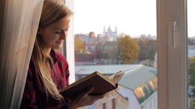 在窗口附近的愉快的妇女阅读书在日落 股票视频