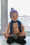 在窗口附近的有条理的一点男婴舒适的开会在冬天衣裳weared 免版税库存图片
