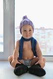在窗口附近的有条理的一点男婴舒适的开会在冬天衣裳weared 库存图片