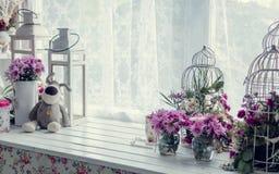 在窗口附近的桃红色和紫色花 免版税库存图片