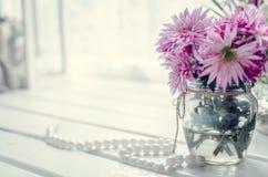 在窗口附近的桃红色和紫色花 库存图片