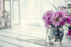 在窗口附近的桃红色和紫色花 图库摄影