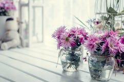 在窗口附近的桃红色和紫色花 免版税库存照片