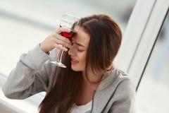 在窗口附近的沮丧的少妇饮用的酒 库存照片