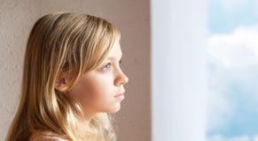 在窗口附近的白肤金发的白种人女孩与蓝天 免版税图库摄影