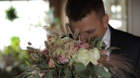在窗口附近的英俊的新郎身分和嗅一束婚姻的花 3花束重点前景婚礼 商人 股票录像