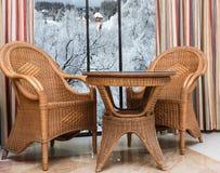 在窗口附近的藤条家具与冬天风景 免版税库存图片