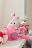 在窗口附近的滑稽的独眼的桃红色玩具 免版税库存图片