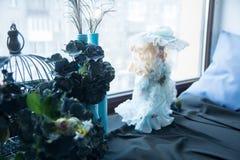 在窗台、人为蓝色花和玩偶上 库存图片