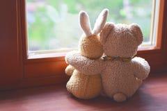 在窗台的两个长毛绒玩具 免版税库存图片
