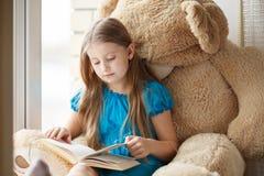 在窗台的小女孩读书与大玩具 免版税库存图片