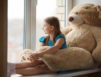 在窗台的小女孩读书与大玩具 图库摄影