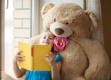 在窗台的小女孩读书与大玩具 库存图片