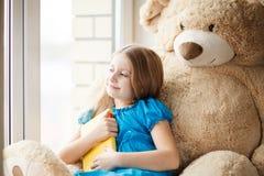 在窗台的小女孩读书与大玩具 免版税库存照片