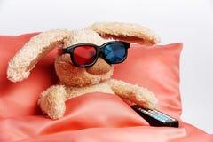 在立体声玻璃的一只玩具兔子与一遥控从电视 免版税库存图片