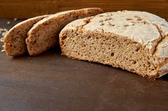 在立即可食木的背景的自创切的开胃新鲜面包 在棕色桌上的被烘烤的鲜美面包 免版税库存图片