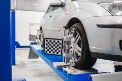 在立场的汽车与传感器轮子对准线反挠度的登记服务站车间  免版税库存照片