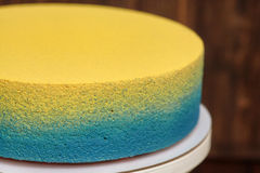 在立场的蓝色和黄蛋糕在木背景 免版税库存照片
