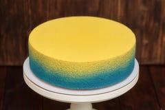 在立场的蓝色和黄蛋糕在木背景 库存照片