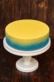 在立场的蓝色和黄蛋糕在木背景 库存图片