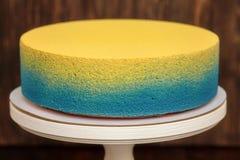 在立场的蓝色和黄蛋糕在木背景 免版税库存图片