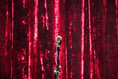在立场的话筒在红色帷幕背景 库存照片