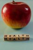 在立方体和苹果写的词健康 免版税库存照片