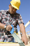 在站点的建筑工人锯切 图库摄影