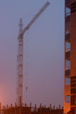 在站点的建筑用起重机,未完成的房子,雾盖顶层,平衡微明 免版税图库摄影