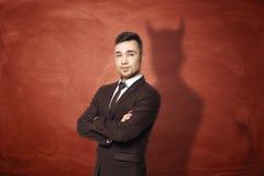 在站立与他的胳膊的衣服的商人折叠了,他投下恶魔的阴影在生锈的橙色墙壁上的在他后 库存图片