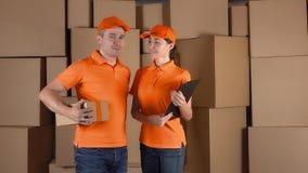在站立反对棕色cartboard的橙色制服的传讯者把backround装箱 个人的运送公司, 4K夹子 股票视频