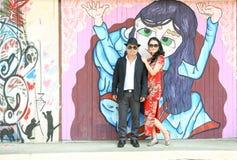 在站立反对街道艺术的中国式礼服和太阳镜的亚洲夫妇 库存照片
