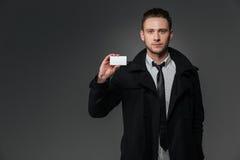 在站立和拿着空白的名片的黑外套的商人 免版税库存照片
