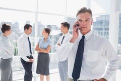 在站立在一个现代办公室的电话的上司 库存图片
