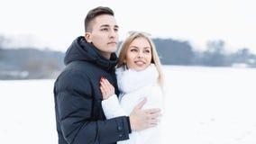 在站立在一个领域的爱的年轻美好的夫妇在一个冬天d 库存图片