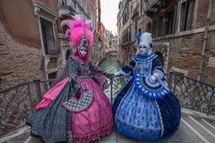 在站立在一座桥梁的服装的两个妇女面具在威尼斯在狂欢节期间 库存图片