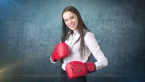 在站立在与红色拳击手套的作战姿势的白色衬衣的年轻美丽的妇女礼服 到达天空的企业概念金黄回归键所有权 库存照片