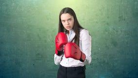 在站立在与红色拳击手套的作战姿势的白色衬衣的年轻美丽的妇女礼服 到达天空的企业概念金黄回归键所有权 免版税库存照片