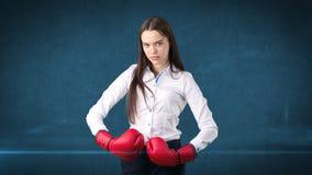 在站立在与红色拳击手套的作战姿势的白色衬衣的年轻美丽的妇女礼服 到达天空的企业概念金黄回归键所有权 图库摄影