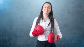 在站立在与红色拳击手套的作战姿势的白色衬衣的年轻美丽的妇女礼服 到达天空的企业概念金黄回归键所有权 免版税库存图片