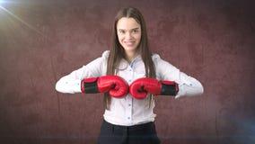 在站立在与红色拳击手套的作战姿势的白色衬衣的年轻美丽的妇女礼服 到达天空的企业概念金黄回归键所有权 库存图片