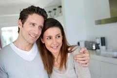 在站立在厨房里的爱的夫妇 免版税库存图片
