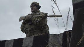 在站立在天空和草背景的一个领域的军队制服和帽子的军事  有一杆枪的一位战士在附近 股票录像