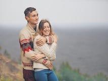在站立在峭壁的被编织的毛线衣的年轻有吸引力的夫妇 免版税库存图片