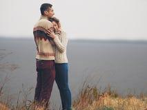 在站立在峭壁的被编织的毛线衣的年轻有吸引力的夫妇 图库摄影