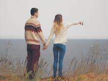 在站立在峭壁的被编织的毛线衣的年轻有吸引力的夫妇 免版税库存照片