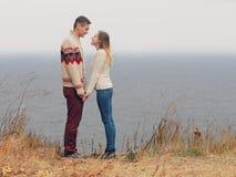 在站立在峭壁的被编织的毛线衣的年轻有吸引力的夫妇 库存照片