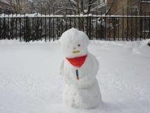 在站立在房子附近的红色围巾的大雪人 库存图片