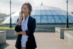 在站立在有一个手机的城市的衣服的愉快的商人 免版税库存照片