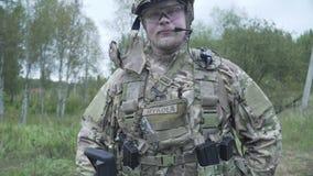 在站立在森林和草背景的一个领域的军队制服和帽子的军事  战士武器 股票录像
